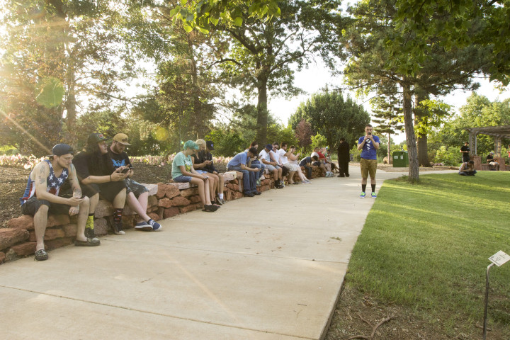 Dozens of Pokemon hunters sit and search for Pokemon in Will Rogers Park in Oklahoma City. There are several Pokestops as well as a gym in Will Rogers park, which makes it an ideal location for playing Pokemon Go. Photo by Ryan Naeve / The Vista.