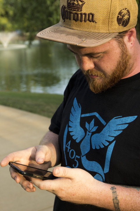 Daniel Jarvis collects items from a Pokestop in Will Rogers Park, Oklahoma City. Jarvis is a member of Team Mystic, one of three teams that Pokemon Go players have the choice to join. Jarvis said he chose team Mystic because he likes their mascot, Articuno. Photo by Ryan Naeve / The Vista.